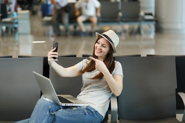 Jonge reizigerstoeristenvrouw die aan laptop werkt die selfie op mobiele telefoon doet die met de vinger op de camera wijst, wacht in de lobbyhal op de luchthaven