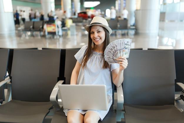 Jonge reizigerstoeristenvrouw die op laptop werkt met een bundel dollars, contant geld, wachtend in de lobby op de internationale luchthaven