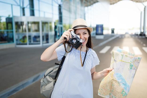 Jonge reizigerstoeristenvrouw maakt foto's op retro vintage fotocamera, houdt papieren kaart vast op internationale luchthaven