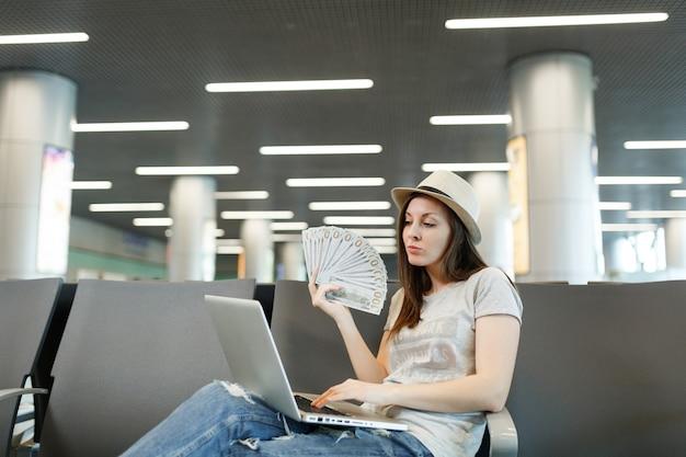 Jonge reizigerstoeristenvrouw met hoed die op laptop werkt, een bundel dollars vasthoudt, contant geld terwijl ze wacht in de lobbyhal op de luchthaven