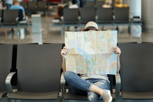 Jonge reizigerstoeristische vrouw die bedekt is met papieren kaart, route zoekt, wacht in de lobby op de internationale luchthaven