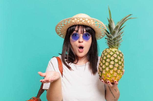 Jonge reizigersvrouw bange uitdrukking en houdt een ananas vast