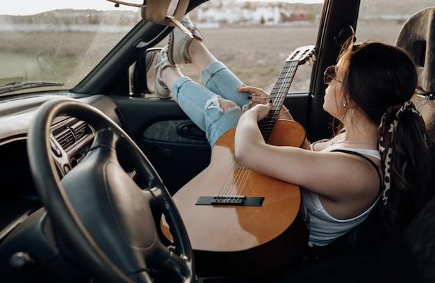 Jonge reizigersvrouw die de gitaar binnen de jeepauto spelen die een zwerflustvakantie maken bij zonsondergang in de zomer