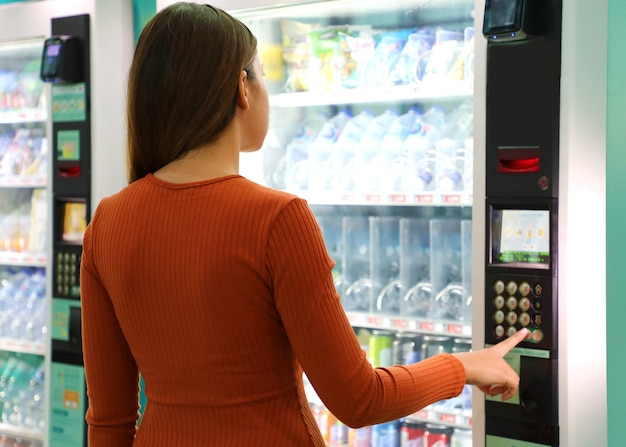 Jonge reizigersvrouw die een hapje of een drankje kiezen bij de automaat op de luchthaven