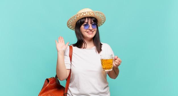 Jonge reizigersvrouw die gelukkig en opgewekt glimlacht, hand zwaait, u verwelkomt en begroet, of afscheid neemt