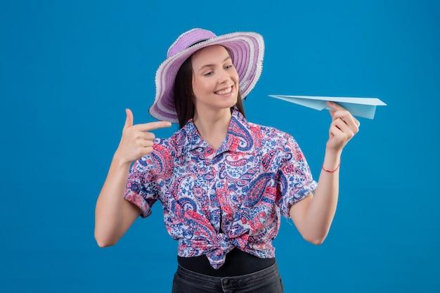 Jonge reizigersvrouw die in de holdingsdocument van de de zomerhoed vliegtuig die met vinger aan het richten glimlachen met gelukkig gezicht over blauwe muur