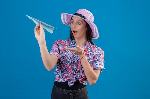 Jonge reizigersvrouw die in de holdingsdocument van de de zomerhoed vliegtuig met wapen van hand aan het kijken die verrast over blauwe muur kijken