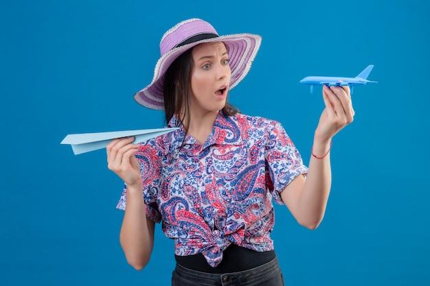 Jonge reizigersvrouw die in de holdingsdocument van de zomerhoed en stuk speelgoed vliegtuigen verbaasd en verbaasd over blauwe achtergrond kijken