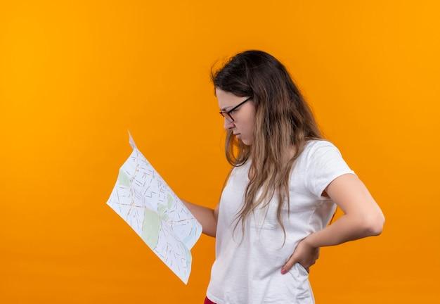 Jonge reizigersvrouw die in de witte kaart van de t-shirtholding het met peinzende uitdrukking op gezicht bekijken die zich over oranje muur bevinden denken