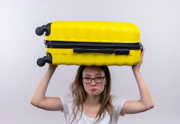Jonge reizigersvrouw die in de witte koffer van de t-shirtholding boven haar hoofd ontevreden en moe kijken die zich over witte muur bevinden