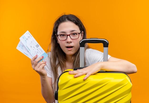 Jonge reizigersvrouw die in de witte koffer van de t-shirtholding en vliegtickets kijken verbaasd status over oranje muur