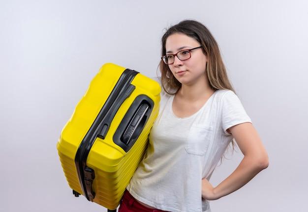 Jonge reizigersvrouw die in de witte koffer van de t-shirtholding opzij verbaasd status over witte muur kijken