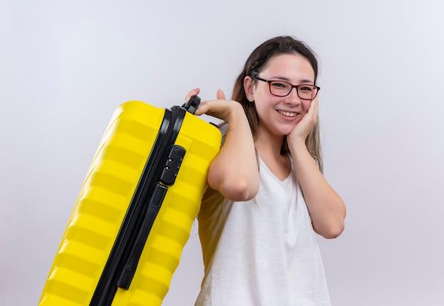 Jonge reizigersvrouw die in de witte koffer van de t-shirtholding verbaasd en verrast gelukkig glimlachen kijken die zich over witte muur bevinden