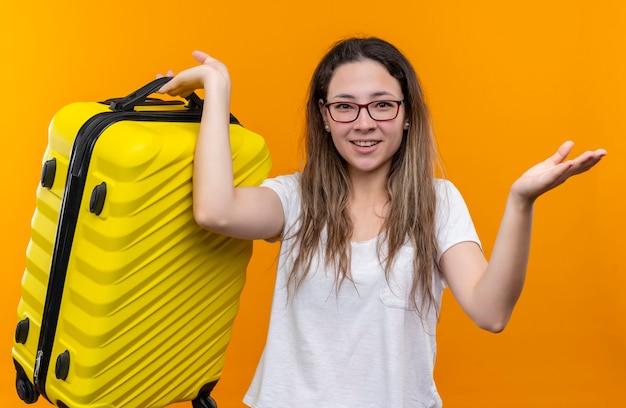 Jonge reizigersvrouw die in de witte koffer van de t-shirtholding verward kijken hebbend twijfels glimlachend status over oranje muur