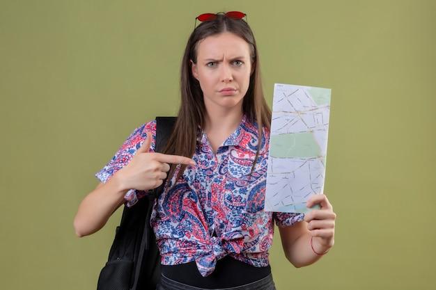 Jonge reizigersvrouw die met rode zonnebril op hoofd en met de kaart van de rugzakholding met wijsvinger aan het met fronsend gezicht over groene muur richten