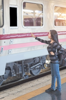 Jonge reizigersvrouw die met rugzak bestemming van leeg computer wit bord controleren alvorens op de trein te krijgen