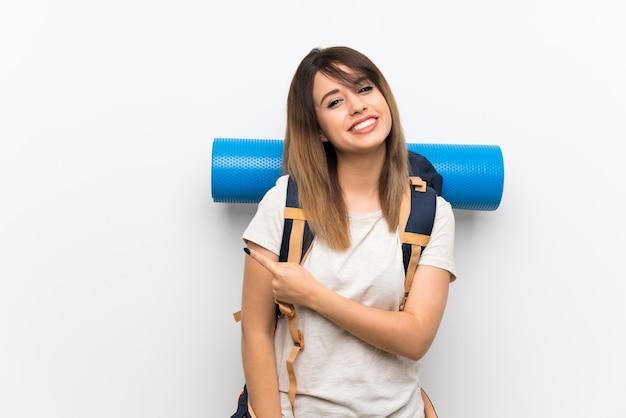 Jonge reizigersvrouw die over witte achtergrond aan de kant richt om een product te voorstellen