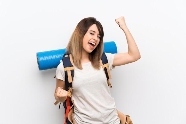 Jonge reizigersvrouw die over witte achtergrond een overwinning viert