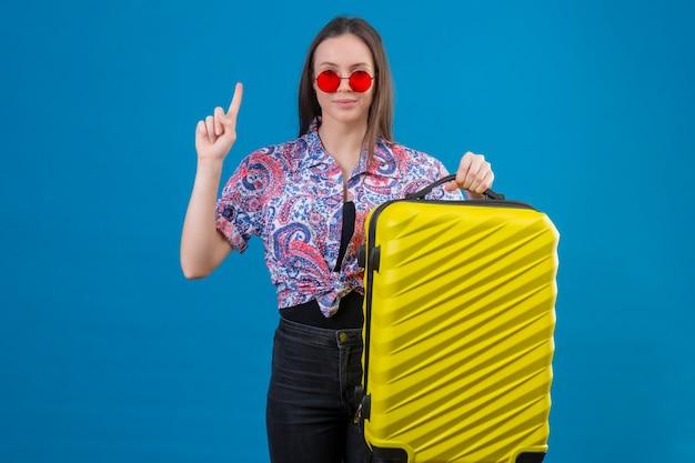Jonge reizigersvrouw die rode zonnebril draagt die gele koffer houdt die met omhoog vinger omhoog staat kijkt zelfverzekerd met geweldig idee over blauwe achtergrond
