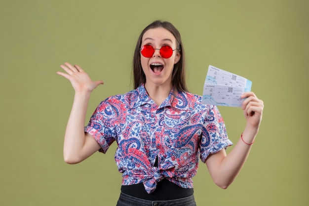 Jonge reizigersvrouw die rode zonnebril draagt die kaartjes houdt verbaasd en verrast met opgeheven wapens die zich over groene achtergrond bevinden