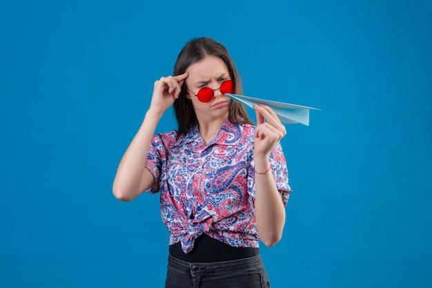 Jonge reizigersvrouw die rode zonnebril dragen die document vliegtuig houden bekijkend het met fronsend ontstemd gezicht twijfelend over blauwe muur