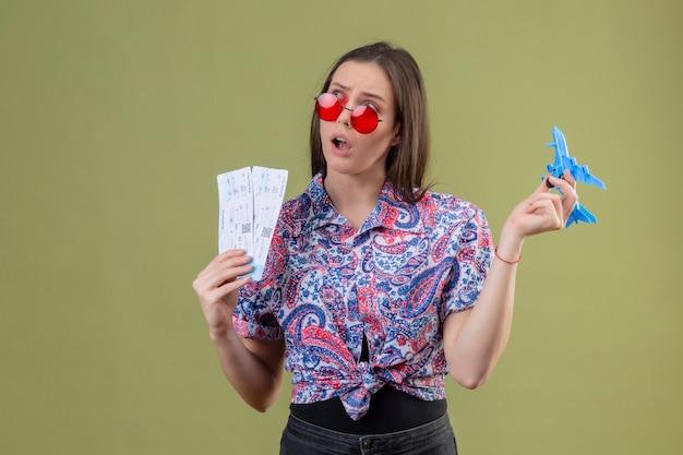 Jonge reizigersvrouw die rode zonnebril dragen die kaartjes en stuk speelgoed vliegtuig houden die opzij met peinzende uitdrukking kijken die zich over groene achtergrond bevindt