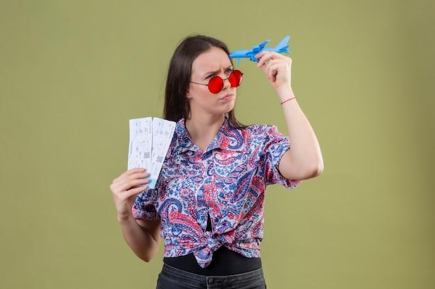 Jonge reizigersvrouw die rode zonnebril dragen die kaartjes en stuk speelgoed vliegtuig houden die opzij met peinzende uitdrukking met fronsend gezicht over groene muur kijken