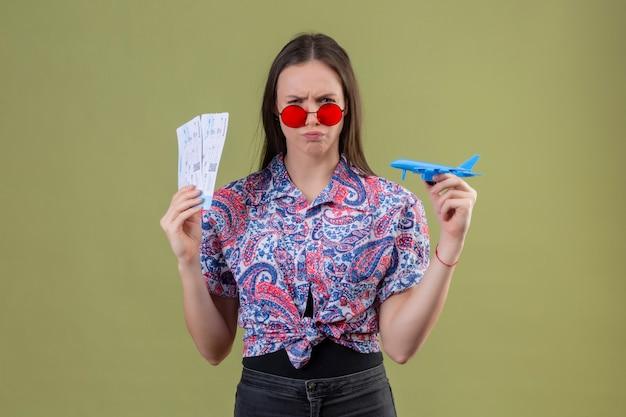 Jonge reizigersvrouw die rode zonnebril dragen die kaartjes en stuk speelgoed vliegtuig met fronsend gezicht houden over groene muur ontevreden