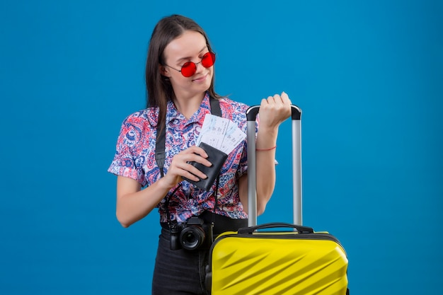 Jonge reizigersvrouw die rode zonnebril dragen die zich met het gele paspoort en de kaartjes van de kofferholding bevinden die opzij positief en gelukkig over blauwe achtergrond kijken