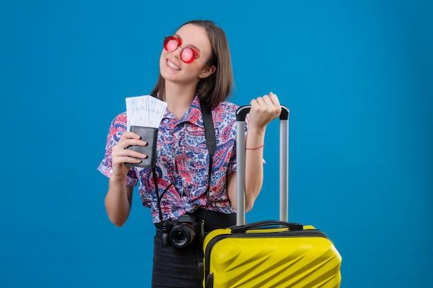 Jonge reizigersvrouw die rode zonnebril met het gele paspoort van de kofferholding en kaartjes dragen die vrolijk met gelukkig gezicht over blauwe muur glimlachen