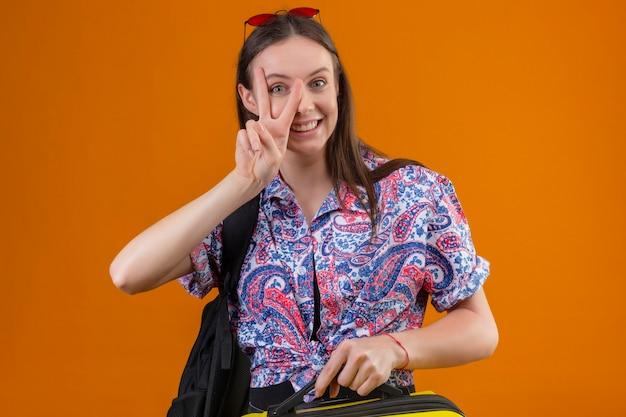 Jonge reizigersvrouw die rode zonnebril op hoofd draagt die zich met rugzak bevindt met koffer kijkt naar camera glimlachend vrolijk doet ok teken kijkt door dit teken staande over oranje bac