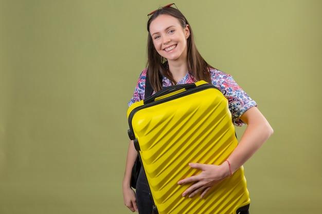 Jonge reizigersvrouw die rode zonnebril op hoofd dragen die zich met de koffer van de rugzakholding bevindt die camera bekijkt die vrolijk met gelukkig gezicht over geïsoleerde groene achtergrond glimlacht