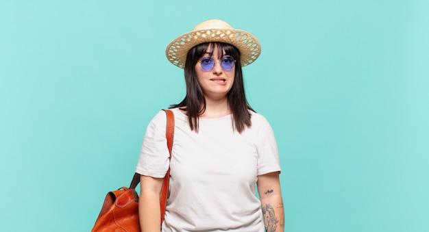 Jonge reizigersvrouw die verbaasd en verward keek, lip bijtend met een nerveus gebaar, het antwoord op het probleem niet wetend