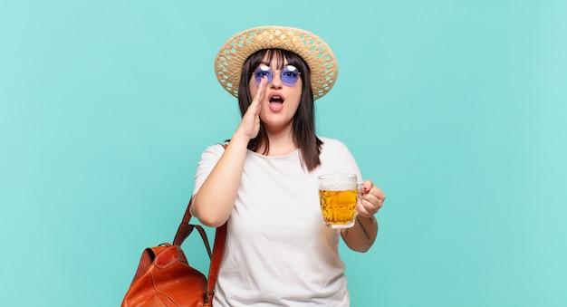 Jonge reizigersvrouw die zich gelukkig, opgewonden en positief voelt, een grote schreeuw geeft met de handen naast de mond, roept