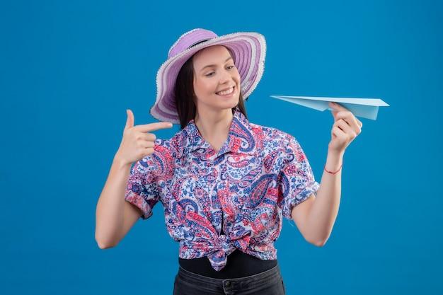 Jonge reizigersvrouw in de holdingsdocument vliegtuig van de zomerhoed die met vinger ernaar richten die met gelukkig gezicht glimlachen die zich over blauwe achtergrond bevinden