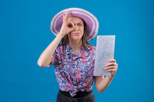 Jonge reizigersvrouw in de holdingskaart die van de zomerhoed ok teken doen die door dit teken met verdachte uitdrukking kijken die zich over blauwe achtergrond bevindt