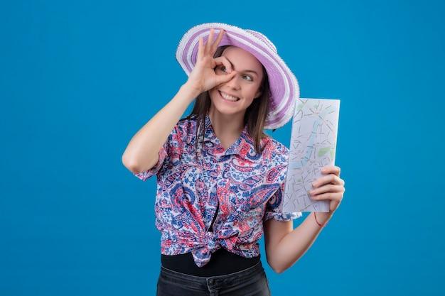 Jonge reizigersvrouw in de holdingskaart van de de zomerhoed positief en gelukkig doet ok teken die door dit teken kijken dat zich over blauwe achtergrond bevindt