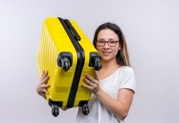 Jonge reizigersvrouw in de witte koffer die van de t-shirtholding gelukkige en positieve status over witte muur glimlachen