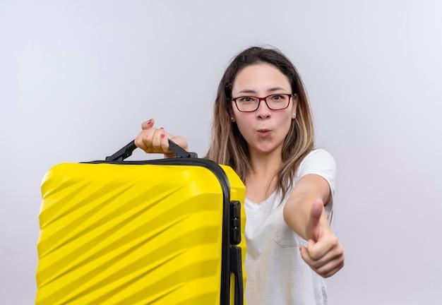 Jonge reizigersvrouw in de witte koffer die van de t-shirtholding opgewekt en gelukkig duimen toont die zich over witte muur bevinden