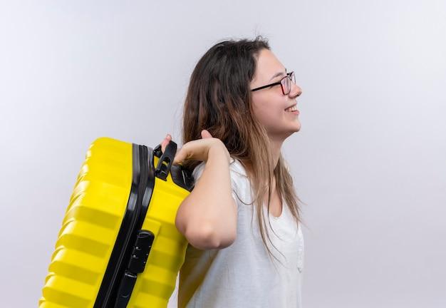 Jonge reizigersvrouw in de witte koffer die van de t-shirtholding zijwaarts glimlachend positief en gelukkig over witte muur staat