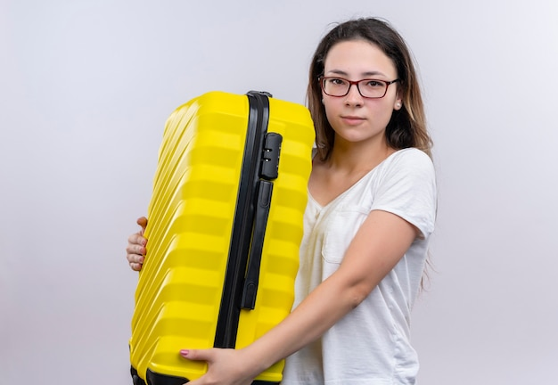 Jonge reizigersvrouw in de witte koffer van de t-shirtholding