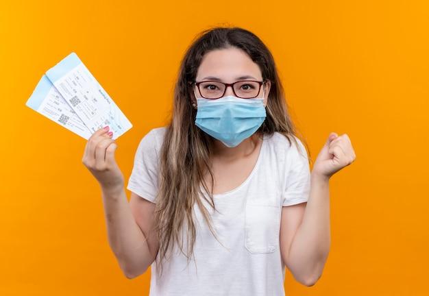 Jonge reizigersvrouw in wit t-shirt die beschermend gezichtsmasker dragen die luchtkaartjes vasthouden, opgewonden en gelukkige vuist vasthoudend over oranje muur