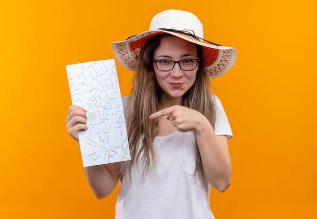 Jonge reizigersvrouw in wit t-shirt die de holdingskaart van de zomerhoed dragen die met vinger ernaar richt die met gelukkig gezicht glimlacht dat zich over oranje muur bevindt