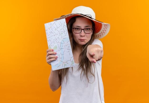 Jonge reizigersvrouw in wit t-shirt die de holdingskaart van de zomerhoed dragen die met wijsvinger aan voorzijde richt
