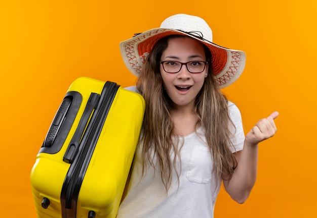 Jonge reizigersvrouw in wit t-shirt die de koffer van de de holdingskoffer van de zomerhoed dragen opgewonden en gelukkige gebalde vuist die zich over oranje muur bevindt