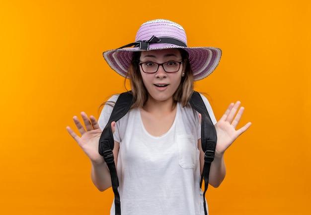 Jonge reizigersvrouw in wit t-shirt die de zomerhoed met rugzak dragen die vrolijk glimlachen kijkt verbaasd status over oranje muur