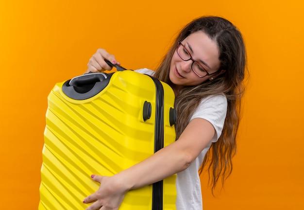 Jonge reizigersvrouw in wit t-shirt die koffer gelukkig en positief koesteren die zich over oranje muur bevinden
