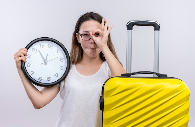 Jonge reizigersvrouw in wit t-shirt die zich met de muurklok van de kofferholding bevinden ok teken doen kijkend door dit teken over witte muur