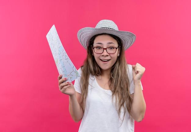 Jonge reizigersvrouw in wit t-shirt en de holdingskaart van de zomerhoed die opgewonden en gelukkige gebalde vuist over roze muur kijken