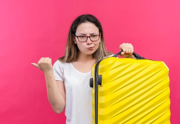 Jonge reizigersvrouw in wit t-shirt met reiskoffer die met de vinger naar de kant wijst en ontevreden kijkt met fronsend gezicht dat zich over roze muur bevindt